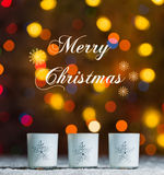 Candles standing in snow with defocussed fairy lights, colourful bokeh in the background, Festive Christmas background stock image