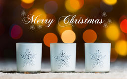 Candles standing in snow with defocussed fairy lights, gold bokeh in the background, Festive Christmas background royalty free stock images