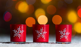 Candles standing in snow with defocussed fairy lights, orange or golden bokeh in the background Royalty Free Stock Image