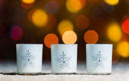 Candles standing in snow with defocussed fairy lights, orange or golden bokeh in the background Royalty Free Stock Images