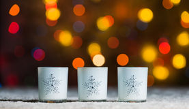 Candles standing in snow with defocussed fairy lights, orange or golden bokeh in the background royalty free stock photos