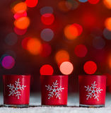 Candles standing in snow with defocussed fairy lights, red bokeh in the background, Festive Christmas background Royalty Free Stock Photos