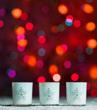 Candles standing in snow with defocussed fairy lights, red bokeh in the background, Festive Christmas background Royalty Free Stock Photo