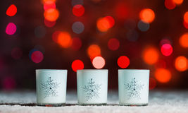 Candles standing in snow with defocussed fairy lights, red bokeh in the background, Festive Christmas background Royalty Free Stock Photography