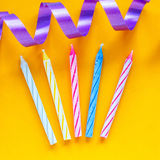 Candles and streamer on yellow background. Preparing for a birthday Royalty Free Stock Photo