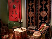 Candles on the table, carpets on the couch and the wall. Room in oriental style. This photo shows Candles on the table, carpets on the couch and the wall. Room Royalty Free Stock Photos