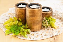Candles. Three brown ancient style candle nests and green leaves on cloth Stock Photo