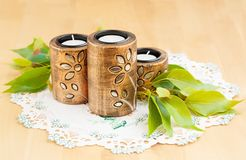 Candles. Three brown ancient style candle nests and green leaves on cloth Royalty Free Stock Photo