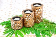 Candles. Three brown ancient style candle nests and green leaves on cloth background Stock Photo