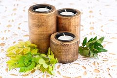 Candles. Three brown ancient style candle nests and green leaves on cloth background Royalty Free Stock Photos
