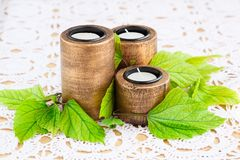 Candles. Three brown ancient style candle nests and green leaves on cloth background Stock Image