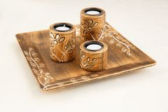 Candles. Three brown ancient style candle nests in plate on cloth background Stock Photo