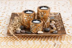 Candles. Three brown ancient style candle nests in plate on cloth background Stock Image