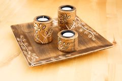 Candles. Three brown ancient style candle nests in plate on wooden background Stock Image
