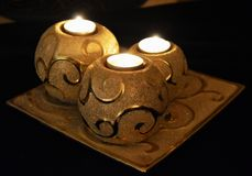 Candles. Three golden and silver glitter ball shaped candle holders Stock Photos