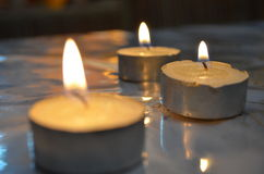 Candles. Three lit tea candles one focused Stock Photo