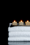Candles on three spa towels on black Royalty Free Stock Image