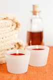 Candles, towels and massage oil. A spa/massage arrangement of candles, towels and massage oil with white background stock images