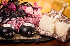 Candles and towels with pink flowers spa concept Stock Photography