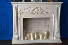 Candles and white fireplace in the room.  Royalty Free Stock Photos