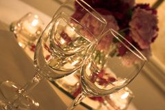 Candles & wine. Wine glasses in front of a floral table decoration - soft light Royalty Free Stock Photos