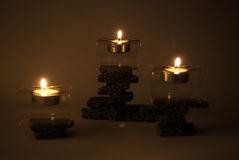 Candles on zen stones. Three lighted candles on balancing stacks of zen stones, dark background Royalty Free Stock Photos