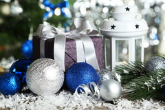 Candlestick with christmas ball and gift box on wooden background Royalty Free Stock Image