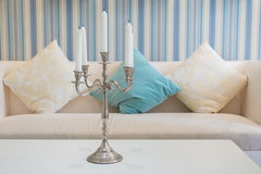 Candlestick with five  candles on table with sofa in background Royalty Free Stock Photography