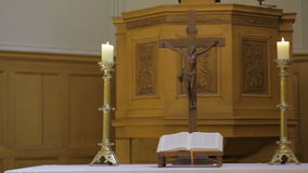 Candlestick holders with crucifix and bible on table in church stock video footage