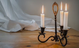 Candlestick. Old candlestick on a wooden table with drape as background stock photo