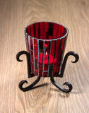 Candlestick from red glass on a metal stand. Stock Photo