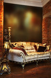 Candlestick and sofa. Ancient candlestick and sofa with pillows in an apartment stock images