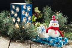 Candlestick in the spruce branches and a snowman with bag on a s Stock Images