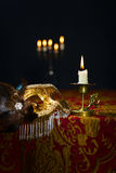Candlestick and Venetian mask. Burning candle in a small brass candlestick and gold carnival mask stock image