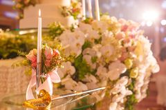 Candlestick and wedding cake cutting sword on the glass table next to the stage in wedding ceremony. Wedding Ceremony tool concept. Candlestick and wedding cake Royalty Free Stock Image