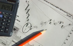 Candlesticks chart. A finance candlestick chart with pen and  pocket calculator Stock Photo