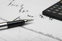 Candlesticks chart, pen and calculator. Close up. Shallow depth of field. Focus on pen Stock Images