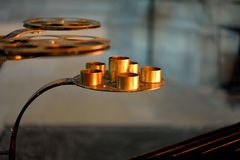 Candlesticks on feet in brass. In the foreground, we perceive several trays in brass, which form carries them candles of the cathedral.The light of wax candles Stock Image
