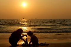 Candolim, Goa, India - 31 gennaio, 2017: figure dei bambini sull'oceano al tramonto fare una piramide della sabbia bagnata immagini stock
