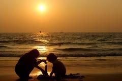 Candolim, Goa, la India - enero, 31, 2017: figuras de niños en el océano en la puesta del sol hacer una pirámide de la arena moja imagenes de archivo