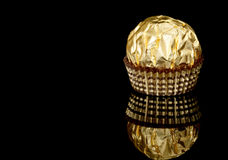 Candy. Wrapped chocolate candy over black background with text space royalty free stock image
