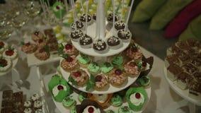 Candy Antivari Una tavola con le caramelle ed i biscotti dolci nei toni verde-arancio su un fondo bianco video d archivio