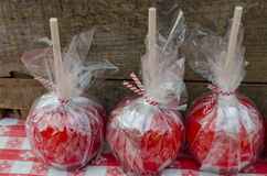 Candy Apples. Red candy apples wrapped in cellophane on a checkered tablecloth are an autumn specialty Royalty Free Stock Images