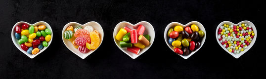 Candy banner in heart-shaped dishes over black Royalty Free Stock Photos