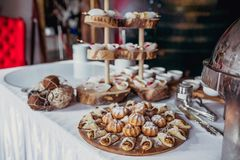 Candy bar on birthday party with a lot of different candies, cupcakes, souffle and cakes. Decorated on wooden stands, nature and e stock photos