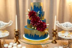 Blue wedding cake decorated by flowers standing of festive table with deserts, strawberry tartlet and cupcakes. Wedding royalty free stock photo