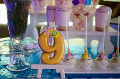 Candy bar on a child`s birthday. Decor with unicorns on the girl. `s holiday. Gingerbread in the form of number nine stock photo