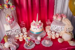 Candy bar for the first birthday for little baby girl. Sweet table and big unicorn cake.  royalty free stock photo