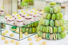 Candy bar with macarons, cakes, cheesecakes, cake pops. Colorful green macaroons pyramide royalty free stock images