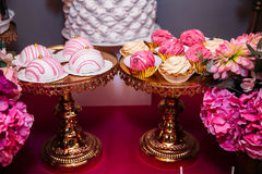 Candy bar marshmallow on the table in a vase, a plate in pink, macaroon, cake and cupcake, holiday, birthday, decoration Royalty Free Stock Images